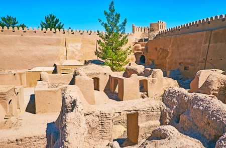 The small living buildings of ancient Rayen citadel are surrounded by huge adobe ramparts with watchtowers and battlements, Iran.