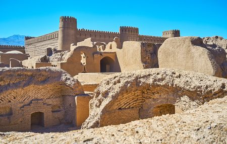 Ruins of the ancient buildings in archaeological site and the massive walls and watchtowers of Rayen castle on the background, Iran.
