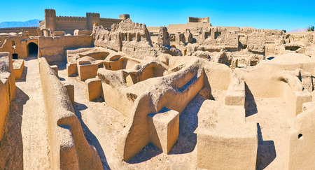 Panorama over the roofs of ancient ruined residential quarters of Arg-e Rayen fortress with towering castle on the background, Iran.