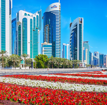 DOHA, CATAR - FEBRUARY 13, 2018: The flower beds are perfect decoration for the modern West Bay neighborhood with its futuristic architecture of business quarters, on February 13 in Doha. Editöryel