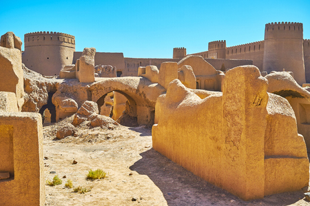 Adobe towers of Rayen castle, rising behind the ruins of residential buildings, Iran.