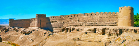 The side outer wall of ancient adobe fortress with battlements, watchtowers and loopholes, Rayen, Iran.
