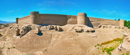 Panorama of ancient deserted adobe citadel with massive defensive walls, numerous watchtowers and rocky hills around it, Rayen, Iran. Stock Photo
