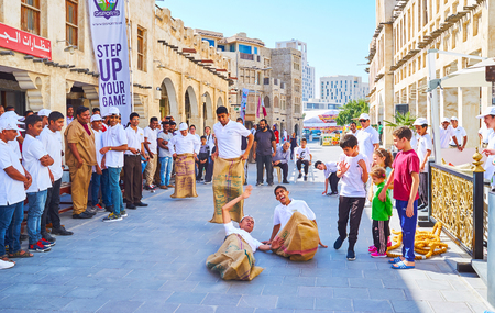 DOHA, QATAR - FEBRUARY 13, 2018: The celebration of Day of Sport - the sack race among the young workers of cafes and restaurants in Souq Waqif, on February 13 in Doha