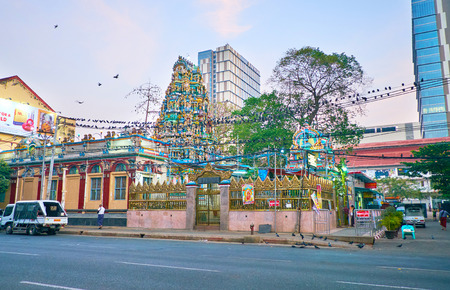 YANGON, MYANMAR - FEBRUARY 16, 2018: The pigeons line up on power wires in front of the Sri Kaali Amman Hindu Temple, located in Little India neighborhood and decorated with colored carved vimana tower, on February 16 in Yangon.
