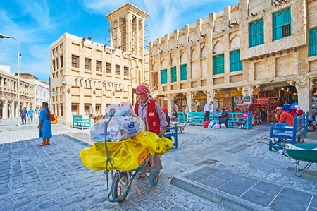 DOHA, QATAR - FEBRUARY 13, 2018: The senior porter at work, carrying goods in wheelbarrow in old street of Souq Waqif, on February 13 in Doha