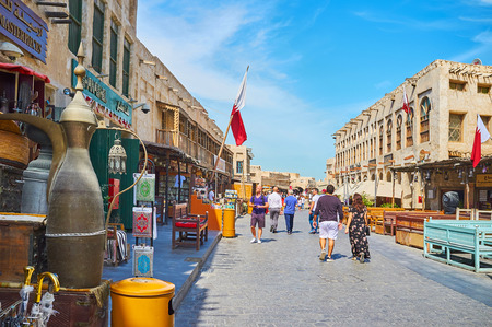 DOHA, QATAR - FEBRUARY 13, 2018: The pleasant walk along the central promenade of Souq Waqif with a view on antique store, outdoor cafes and souvenir stalls, on February 13 in Doha Editorial
