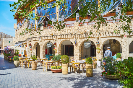 Traditional mansion with shady arcade, projecting wooden beams (shandal), outdoor terrace of the restaurant and numerous plants in large adobe pots, Souq Waqif, Doha, Qatar. Stockfoto