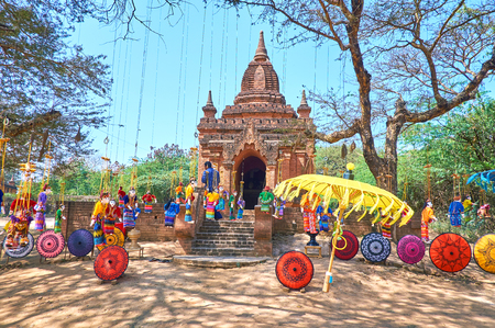 Myanmar beautiful handcrafted umbrellas and hanged puppets attracts tourists to toy exhibition market next to ancient shrines in Bagan Stock Photo