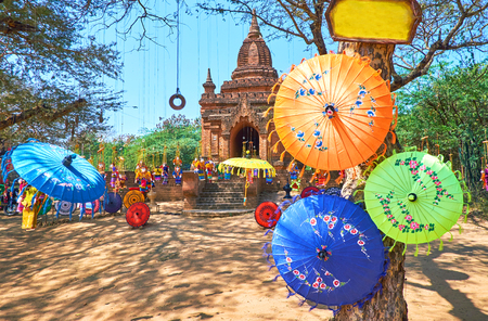 Traditional colored umbrellas and beautiful dolls are hanging on the tree next to the ancient Buddhist Shrine in archaeological site, Bagan, Myanmar