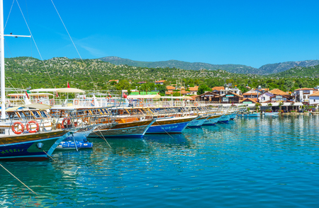 KALEKOY, TURKEY - MAY 5, 2017: The harbor of Ucagiz village located in lagoon (liman), its calm waters reflect the moored yachts, green mountains and small cottages in coastal zone, on May 5 in Kalekoy.