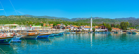 KALEKOY, TURKEY - MAY 5, 2017: The seascape of Kekova bay with a view on mountain landscape of Ucagiz village, scenic cottages, white minaret of local mosque and yachts in harbor, on May 5 in Kalekoy.
