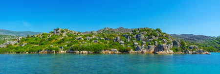Archaeological site of ancient Lycian Necropolis, located on the rocky slope and surrounded by Taurus mountains and waters of Kekova bay, Ucagiz, Turkey.