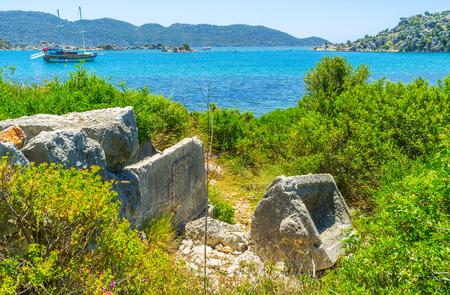 The ruins of the stone tombs of ancient Lycian Kekova Necropolis, located on the rocky coast, Ucagiz, Turkey. Stock Photo