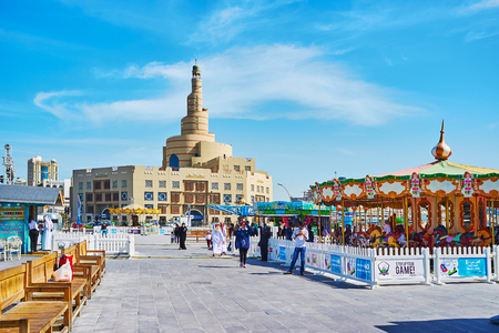 DOHA, QATAR - FEBRUARY 13, 2018: The street of Al Souq district with carousels of Luna park and the scenic building of Al Fanar mosque on the background, on February 13 in Doha. Editorial