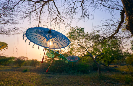 Romantic sunset in Bagan archaeological park with hanged burmese style umbrellas Reklamní fotografie