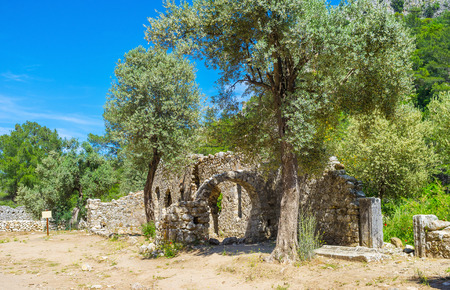 The stone ruins in archaeological site of ancient Lycian town of Olympos, located in river valley at the mountain foot, next to the coast, Turkey.