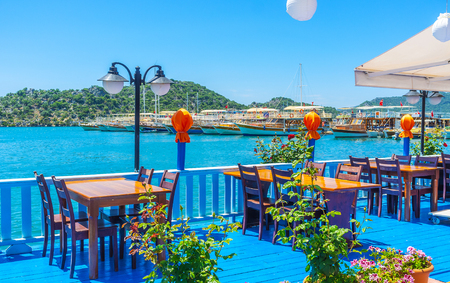 The bright blue wooden terrace of outdoor cafe with a view on yachts and boats in harbor of Ucagiz, Kekova, Turkey.