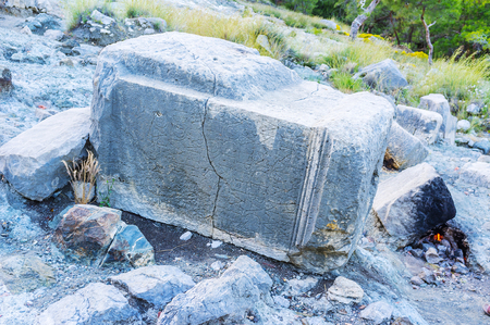 The ruins of ancient Roman column at the small fire on volcanic tract in Chimera site, Yanartas, Turkey. Stock Photo