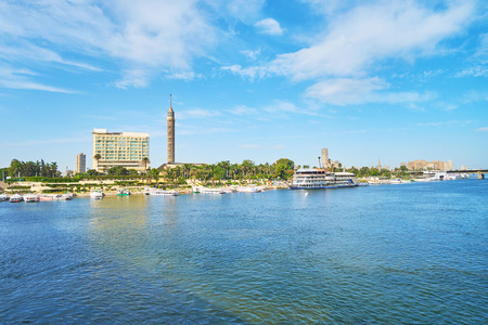 The pleasure boats are moored in port of Gezira Island with a view on lush gardens and Cairo Tower on the background, Cairo, Egypt. Stock Photo