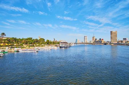 The bank of Gezira Island is covered with lush greenery of Andalus garden, here locates the tourist port with rental boats, Cairo, Egypt. Banco de Imagens