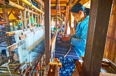 INLE LAKE, MYANMAR - FEBRUARY 18, 2018: Producing of silk textile on the old traditional hand loom in workshop, located  on Inle lake in Inpawkhon village, on February 18 in Inle lake. Standard-Bild - 101240127