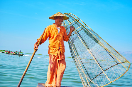 INLE LAKE, MYANMAR - FEBRUARY 18, 2018: The smiling Burmese  fisherman with paddle and net during his daily performance on the lake, on February 18 in Inle lake.