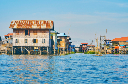 The wooden buildings of Intha village form the streets along the narrow canals of Inle Lake, Myanmar.