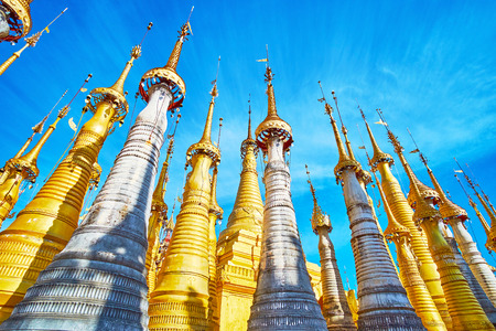 The row of golden hti decorative umbrellas with bells and wind vanes on the top of small stupas, located in site of Inn Thein Buddha image Shrine, Indein (Inn Thein) village, Inle Lake, Myanmar.