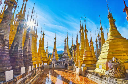 The sun is breaking through the wind vanes and hti umbrellas of golden stupas of Inn Thein Buddha image Shrine, Indein, Inle Lake, Myanmar.
