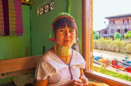 INLE LAKE, MYANMAR - FEBRUARY 18, 2018:  The portrait of Padaung Kayan long neck woman, sitting at the window of the workshop, on February 18 on Inle lake. Standard-Bild - 101461599