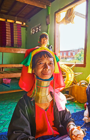 INLE LAKE, MYANMAR - FEBRUARY 18, 2018:  The portrait of senior Padaung Kayan long neck woman in traditional colorful headscarf and numerous brass rings on her neck, on February 18 on Inle lake. Standard-Bild - 101461600