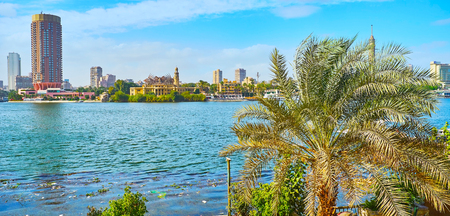 Enjoy the beautiful garden on the bank of Nile with lush green palm trees and view on Gezira Island, Cairo, Egypt.