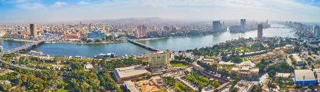 CAIRO, EGYPT - DECEMBER 24, 2017: The landscape with a view on Downtown architecture, numerous bridges across the Nile river and green gardens of Gezira Island, on December 24 in Cairo. Sajtókép