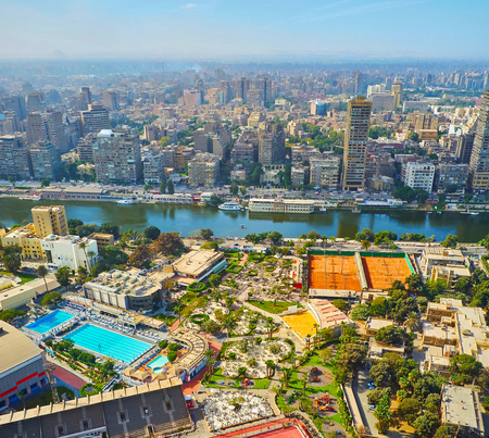 The light morning haze over the dense buildings of Giza with a view on greenery of Gezira Island from the top of Cairo Tower, Egypt.