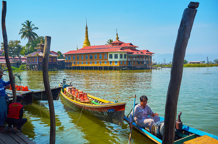YWAMA, MYANMAR - FEBRUARY 18, 2018: The view on the Buddhist Monastery through the old wooden poles for mooring of kayaks in harbor on Inle Lake, on February 18 in Ywama. Éditoriale