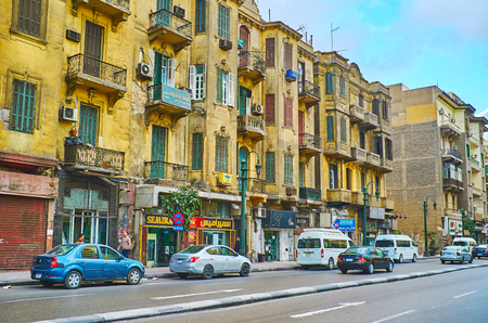 CAIRO, EGYPT - DECEMBER 24, 2017:  The old shabby buildings with peeling plaster stretch along the Qasr Al Nil street of Downtown, on December 24 in Cairo Redakční
