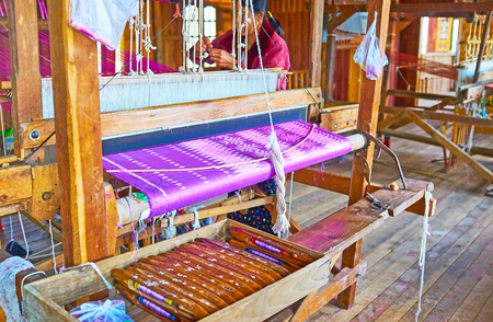 INPAWKHON, MYANMAR - FEBRUARY 18, 2018: Handmade textile production is one of the main handicrafts on Inle Lake, local workshops offer silk and cotton fabrics of imported yarn and lotus fabrics of locally grown plants, on February 18 in Inpawkhon.