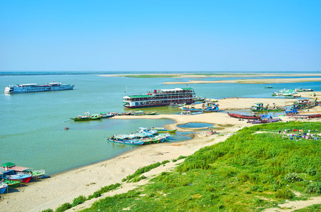 The view on small rural port located on the Irrawaddy river with moored tourist and old fishing boats, Bagan, Myanmar