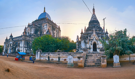 BAGAN, MYANMAR - FEBRUARY 24, 2018:  Panorama of Thatbyinnyu Temple and nearby standing pagoda during sunset, on February 24 in Bagan