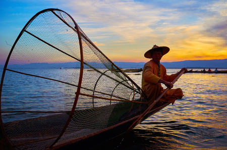 INTHA, MYANMAR - FEBRUARY 18, 2018: The portrait of Burmese fisherman, sitting in his kayak with a addle and large conical net on sunset on Inle Lake, on February 18 in Intha. Editorial