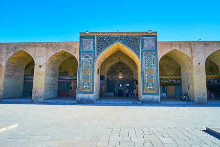 KERMAN, IRAN - OCTOBER 15, 2017: The facade of Ganjali Khan Hammam (bathhouse), facing same named square and decorated with a portal, boasting fine tilework, on October 15 in Kerman.