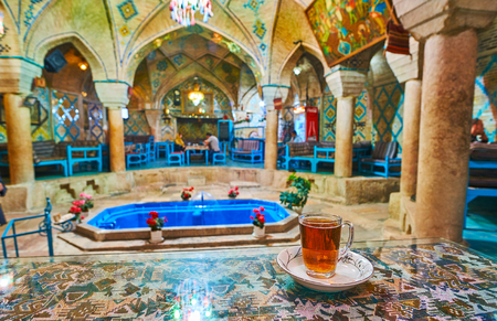 KERMAN, IRAN - OCTOBER 15, 2017: The cup of traditional Persian tea on the table in Vakil restaurant and teahouse, located in building of the former bath with splendid historical interior, on October 15 in Kerman.