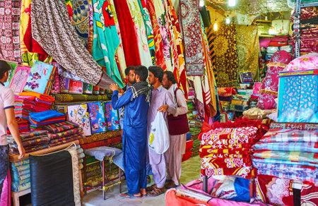 KERMAN, IRAN - OCTOBER 15, 2017: Baluch man choose the blankets and linens in market stall of Ganjali Khan Bazaar, on October 15 in Kerman.