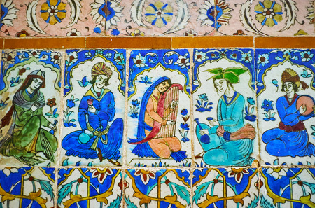 KERMAN, IRAN - OCTOBER 15, 2017: The close-up of tilework in Ganjali Khan Bathhouse, ceramic tiles are covered with depiction of musicians in traditional attire with ethnic instruments, on October 15 in Kerman.
