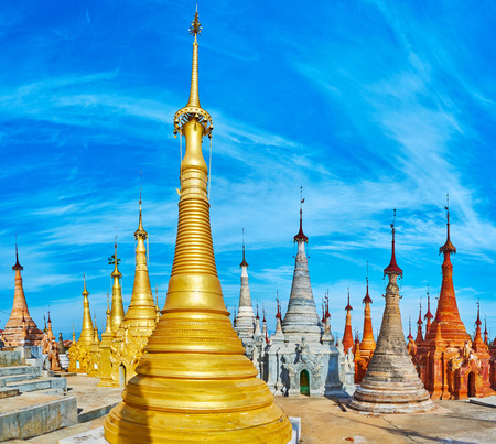 Nyaung Ohak archaeological site boasts stupas of different shape and color, here located white, ochre and golden pagodas, decorated with scenic carved patterns, Inn Thein (Indein) village, Myanmar. Stock Photo