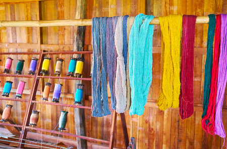 The hand-dyed cotton and lotus yarn dries on the wooden pole in texile workshop of Inpawkhon village, Inle Lake, Myanmar.