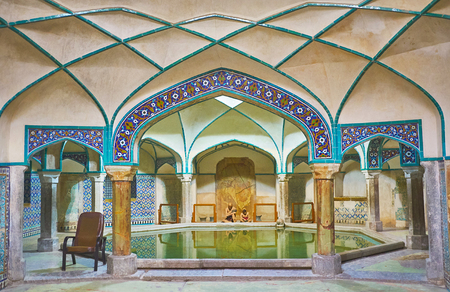 KERMAN, IRAN - OCTOBER 15, 2017: Octagonal swimming pool of Hammam-e Ganjali Khan is seen through the tiled arches of the bathing hall, on October 15 in Kerman.