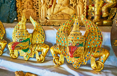 Sculptures of golden Garuda mythical birds, decorated with inlays in market of Inn Thein village on Inle Lake, Myanmar.