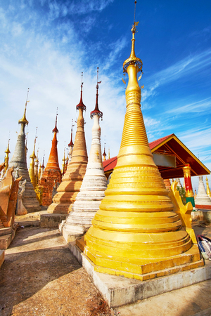 The restored golden stupa among the ancient white, ochre and grey stupas in Nyaung Ohak Buddhist site, Inn Thein, Inle Lake, Myanmar.